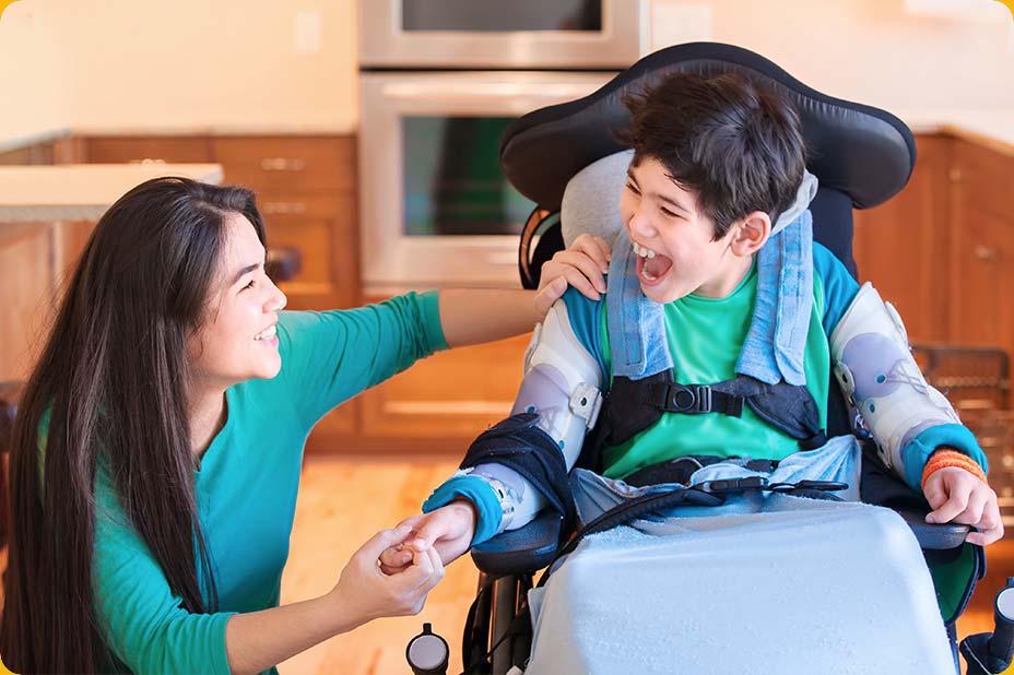 Photo d'un enfant handicapé riant avec une intervenante