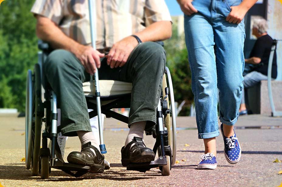Photo d'une personne en fauteuil roulant accompagnée lors d'une promenade