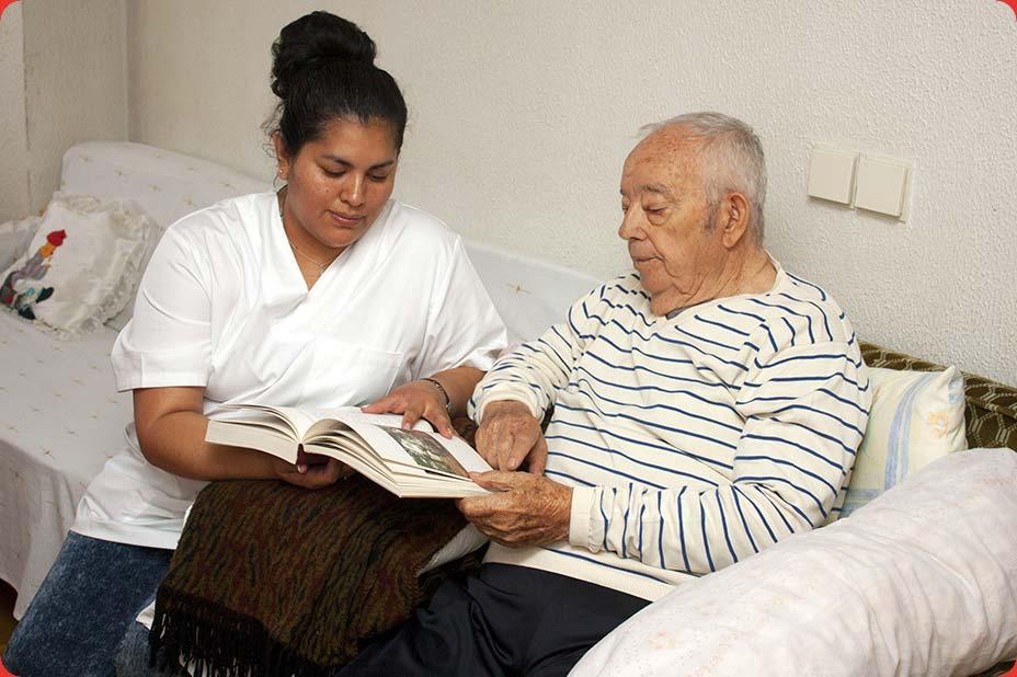 Photo d'une intervenante lisant un livre à un senior