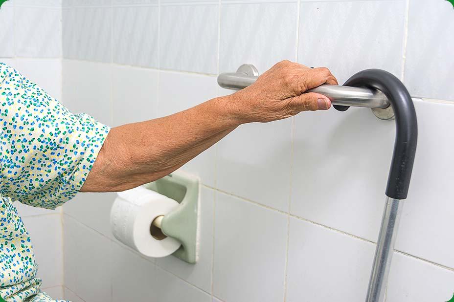 Photo d'une personne âgée avec une canne s'appuyant sur une rampe murale dans ses toilettes
